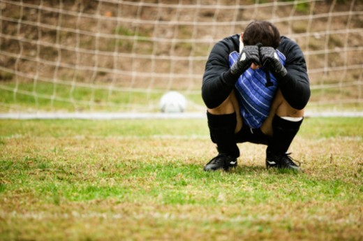 Stock Photo: 1555R-333098 Crouching soccer goalie covering face