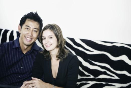 Couple sitting on zebra print sofa : Stock Photo