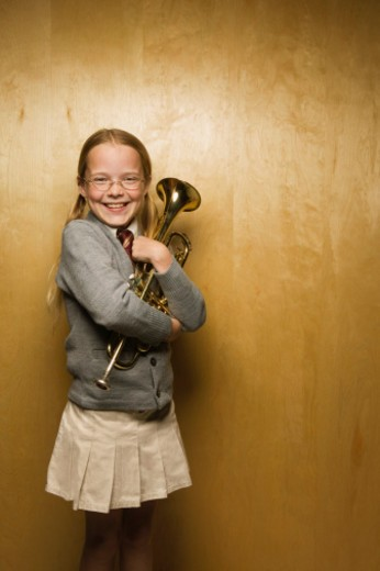 Smiling girl hugging her trumpet : Stock Photo