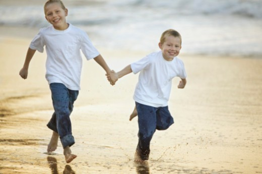 Brothers running on beach holding hands : Stock Photo