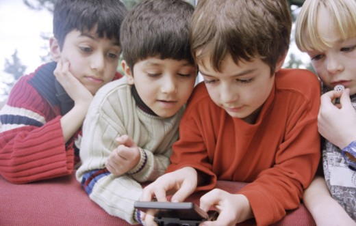 Friends sharing a handheld video game : Stock Photo