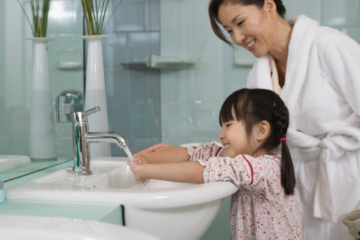 Mother helping daughter wash hands : Stock Photo