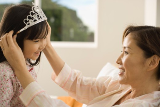 Woman placing tiara on daughter's head : Stock Photo
