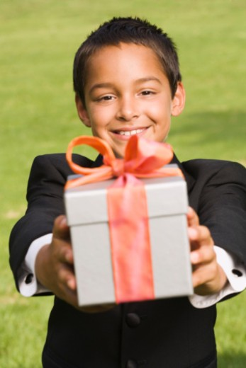 Stock Photo: 1555R-336153 Boy holding gift for quinceanera