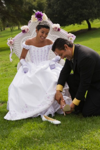 Father putting on teenage girls shoes at quinceanera : Stock Photo