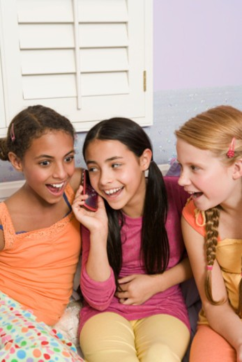 Preteen girls gossiping with cell phone : Stock Photo