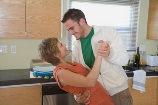 Stock Photo: 1555R-336480 Mid-adult couple dancing in kitchen