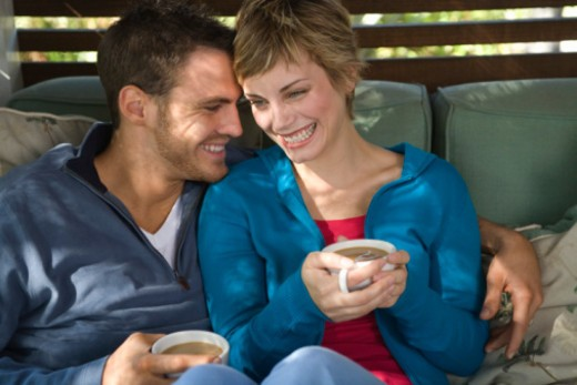 Mid-adult couple in intimate pose with coffee : Stock Photo