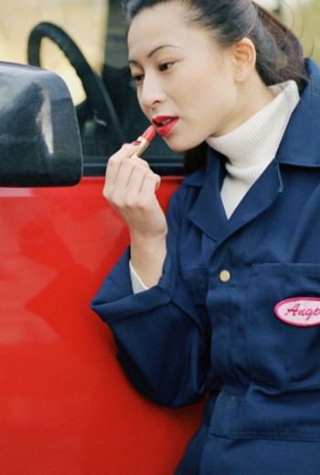 Woman putting on lipstick : Stock Photo