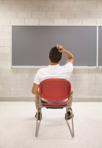 Stock Photo: 1555R-339074 Confused student facing chalkboard in a classroom by himself