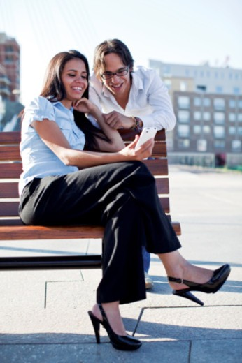 Stock Photo: 1555R-339139 Hispanic Couple using cell phone