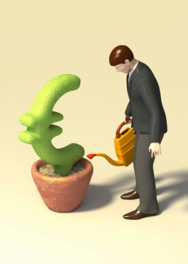 Man watering a Euro symbol topiary : Stock Photo