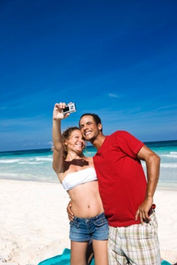 Couple taking picture on beach : Stock Photo