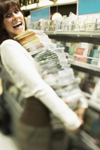 Excited woman in music store carrying a stack of CDs : Stock Photo