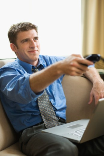 Man working at home distracted by television : Stock Photo