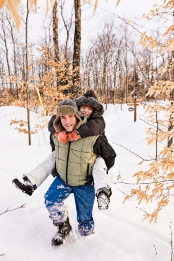 Father giving daughter piggyback ride in snow : Stock Photo