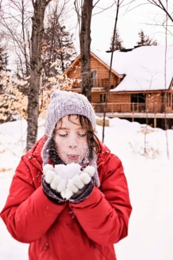 Girl blowing snow from hands : Stock Photo