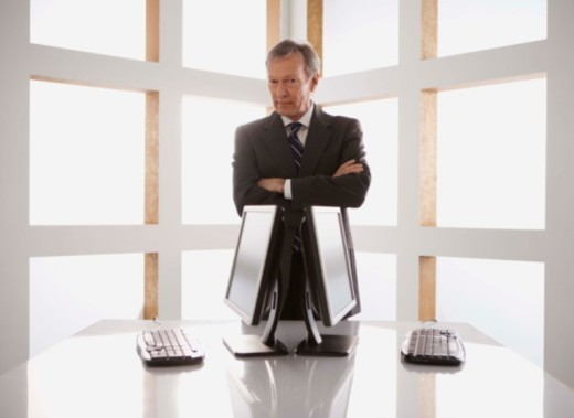Stock Photo: 1555R-341978 Businessman standing by computers