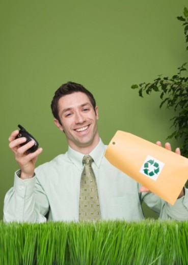 Businessman recycling cell phone : Stock Photo