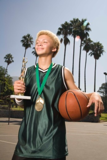 Teenage boy on basketball court with trophy and medal : Stock Photo