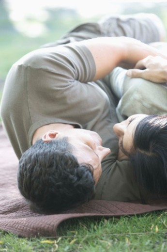 Stock Photo: 1555R-342467 Couple lying on a blanket in the park