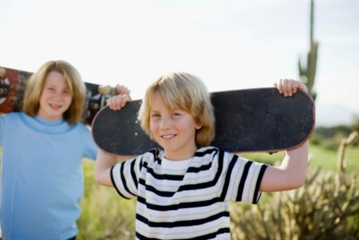 Boys with skateboards on rural road, Arizona : Stock Photo