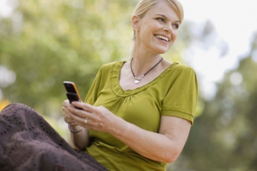 Woman texting on cell phone outdoors : Stock Photo