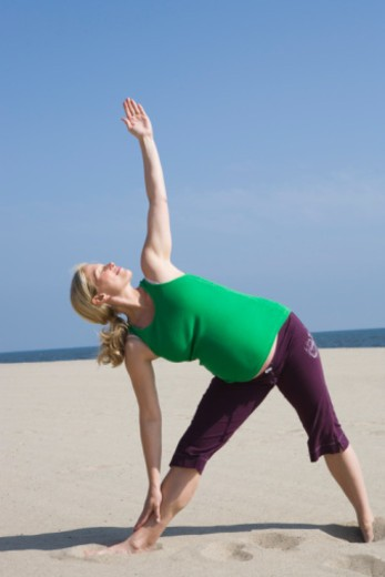 Pregnant woman in Triangle pose : Stock Photo