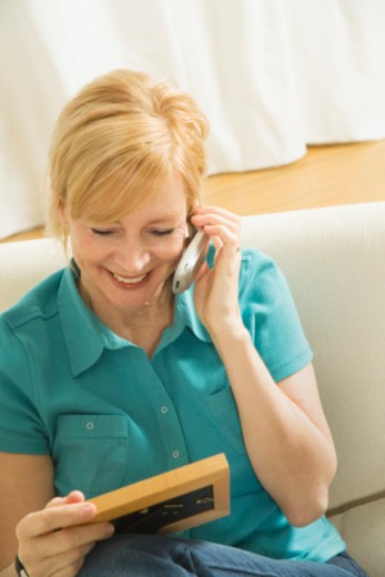 Woman talking on telephone and holding picture : Stock Photo
