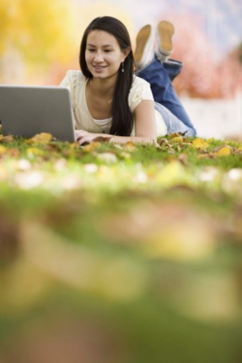 Stock Photo: 1555R-344353 Teenage girl using laptop outdoors