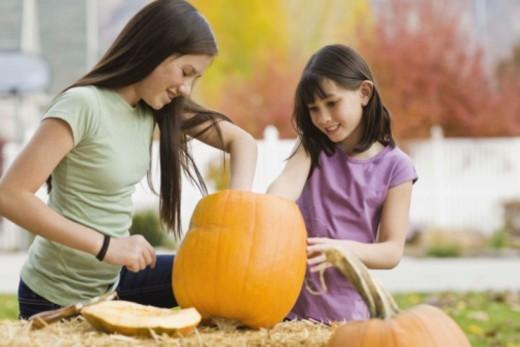 Girls carving pumpkin : Stock Photo
