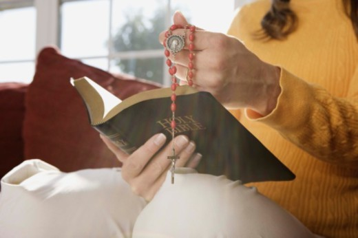 Stock Photo: 1555R-344633 Woman holding prayer beads and Holy Bible indoors