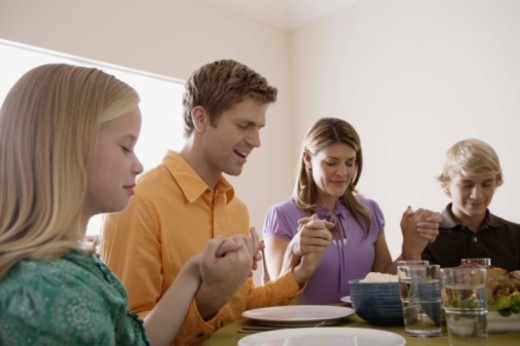 Family holding hands and praying over food at dinner table : Stock Photo