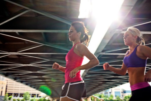 Two girlfriends jogging and exercising together in an urban area of a city. : Stock Photo
