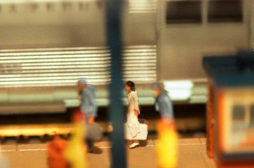 Baggage handlers carrying woman's luggage past train : Stock Photo