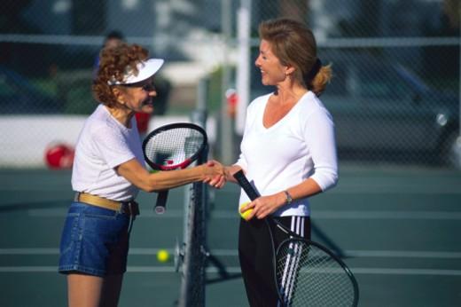 Stock Photo: 1555R-36011 Women tennis partners shaking hands