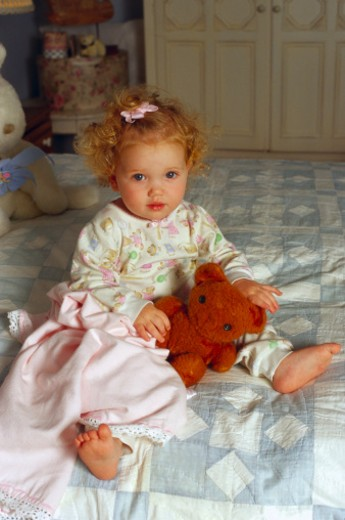 Stock Photo: 1555R-38061 Girl holding teddy bear on bed
