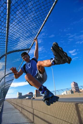 Stock Photo: 1555R-43027 Inline skater grinding on railing