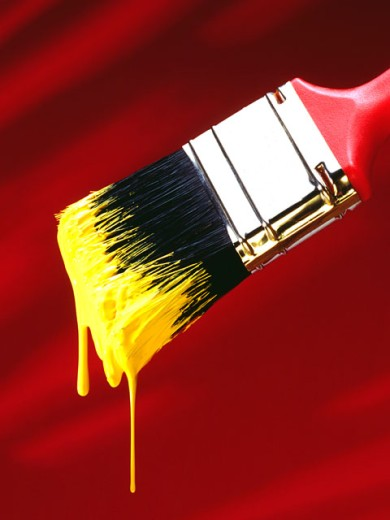 Brush dripping with yellow paint : Stock Photo