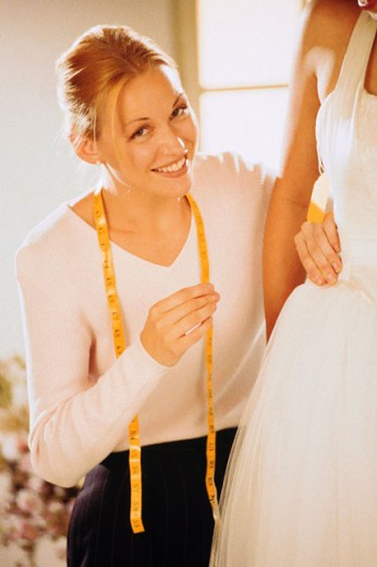 Seamstress fitting wedding dress on client : Stock Photo