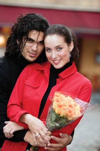 Couple embracing outdoors and holding bouquet : Stock Photo