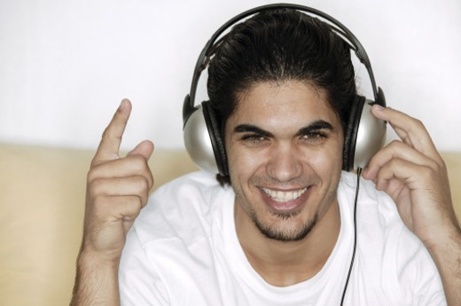 Man listening to headphones and pointing : Stock Photo