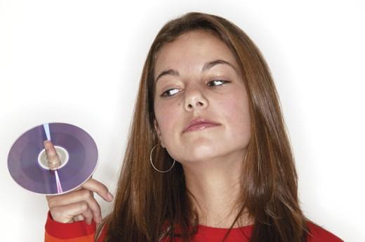 Stock Photo: 1557R-01817 Teenage girl looking at CD