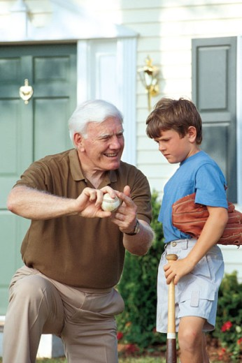 Grandfather showing baseball to grandson : Stock Photo