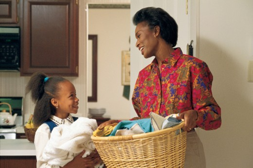 Mother and daughter doing laundry : Stock Photo