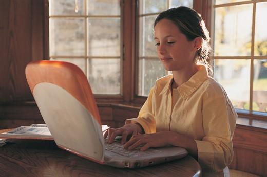 Girl using a laptop : Stock Photo