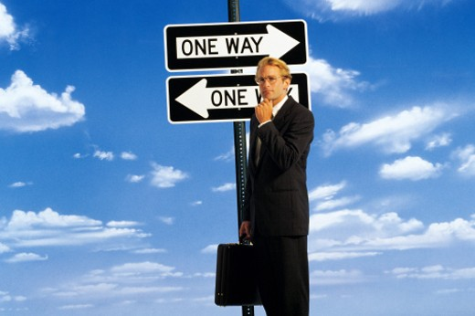 Businessman with one way signs pointing in opposite directions : Stock Photo