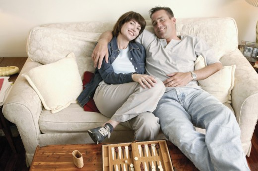 Stock Photo: 1557R-03674 Couple relaxing on couch near backgammon game