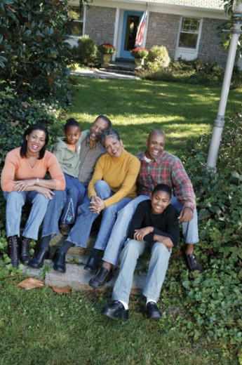 Family laughing while sitting in yard : Stock Photo