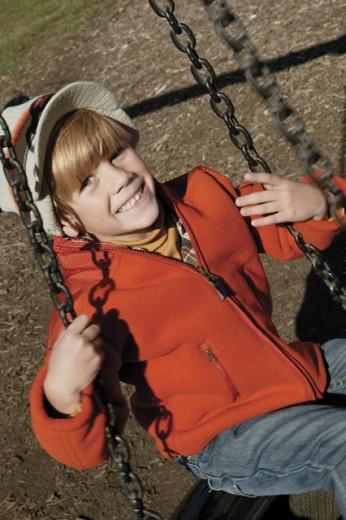 Stock Photo: 1557R-03803 Smiling boy sitting on swing